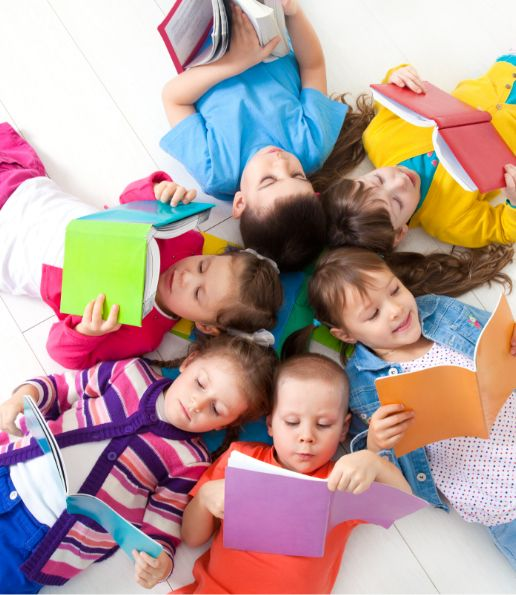 Children laying down together reading books. Colorful clothes. Image represents STEAM learning